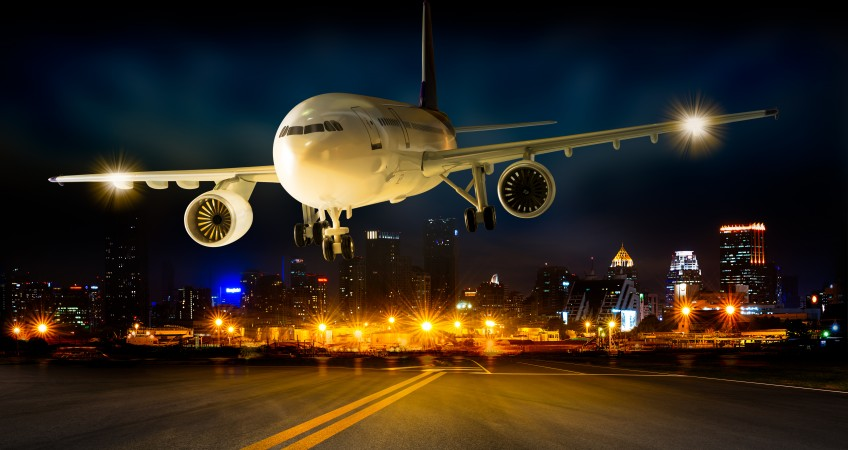 Landing business airplane to the airport runway in the night scene cityscape background